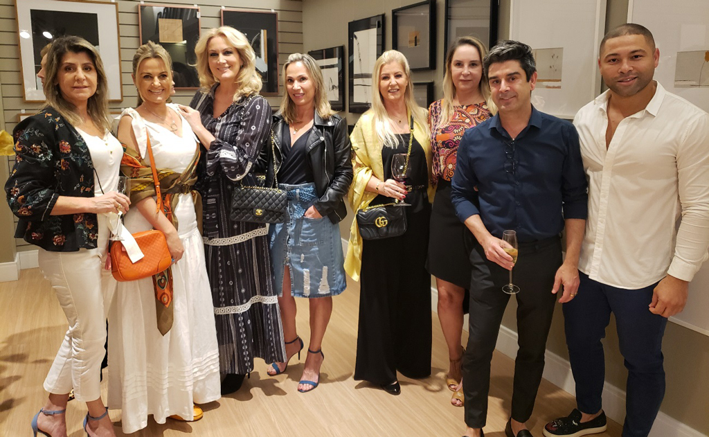 Grupo de arquitetas e empresarias, no evento, admiram trabalhos em aquarela